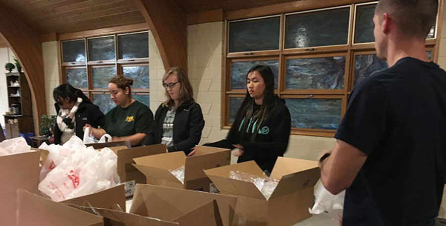 Members of the Chi Sigma chapter of Phi Theta Kappa international honor society at CCC-Columbus assemble food packages that can be put in a backpack that kids can take home from school for weekend consumption.
